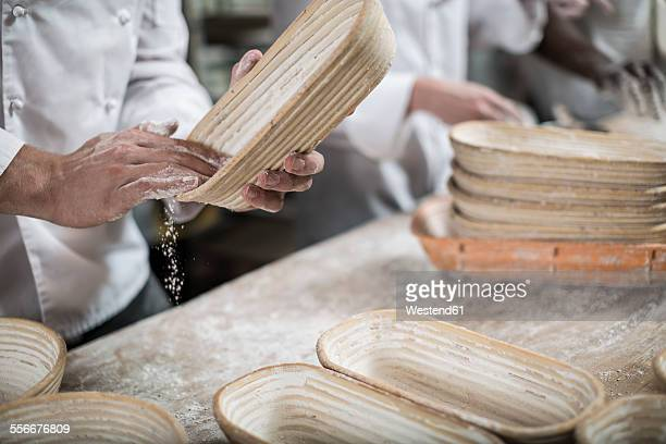 Baker preparing ceramic bowls for baking bread