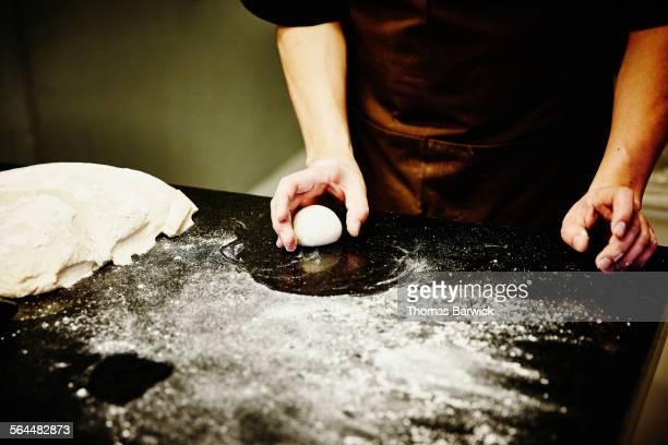Baker preparing dough for pastry in kitchen