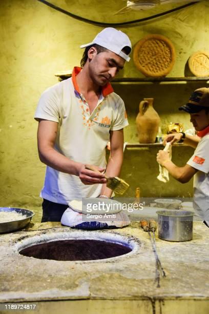 baker preparing nan bread in urumqi - sergio amiti stock pictures, royalty-free photos & images