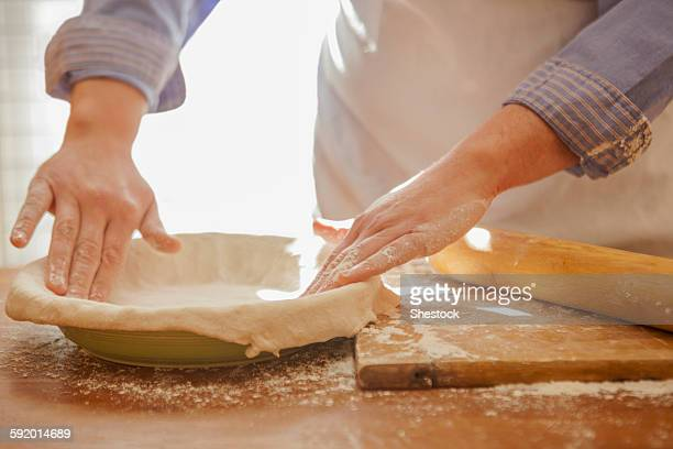 Baker pressing pie dough in dish