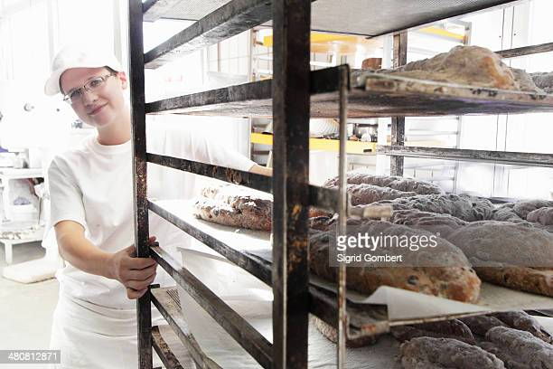 baker pulling trolley of bread - sigrid gombert stock pictures, royalty-free photos & images