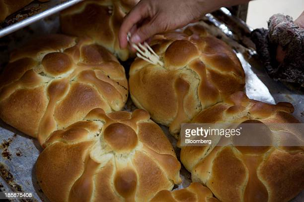 A baker puts a plastic skeleton inside a loaf of pan de muerto at La Ideal bakery in Mexico City Mexico on Thursday Oct 24 2013 The pan de muerto or...