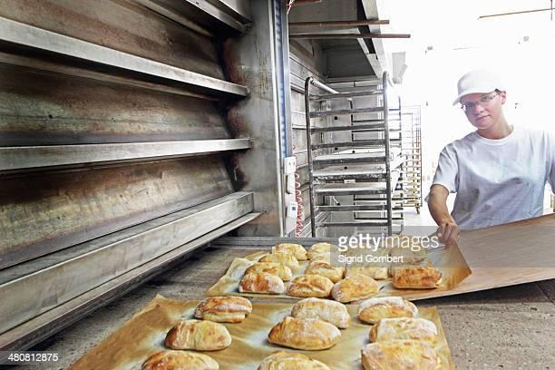 baker putting bread onto baking sheet - sigrid gombert stock-fotos und bilder