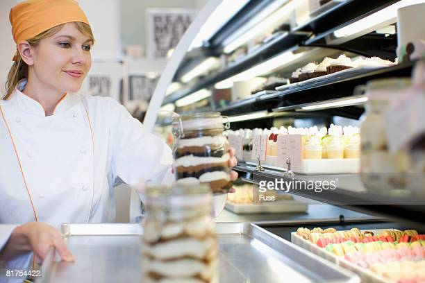 Baker Putting Dessert in Display Case