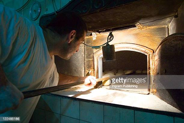 A baker removes freshly baked bread from his wood fire oven, Malta.