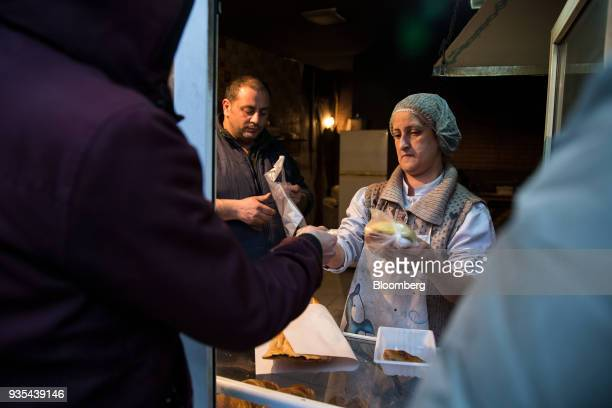 A baker sells goods to customers in Baku Azerbaijan on Sunday March 18 2018 Azerbaijan's economy barely returned to growth last year increasing 01...