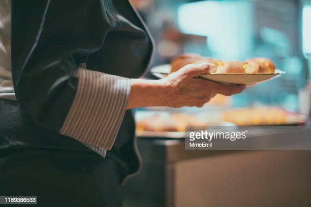 baker serving mini lemon pies on a tray - mmeemil stock photos and pictures