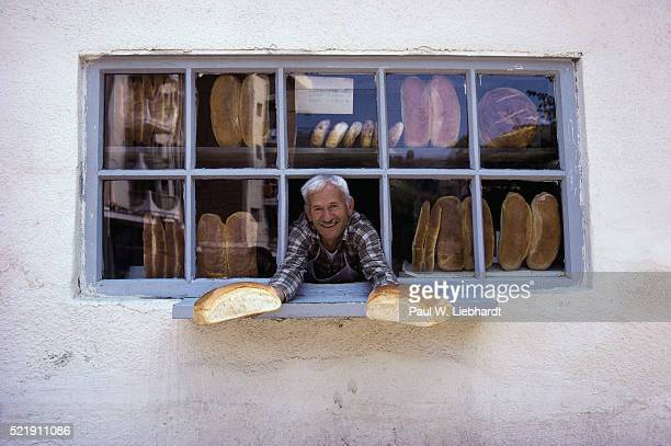 Baker Showing off Loaves of Bread