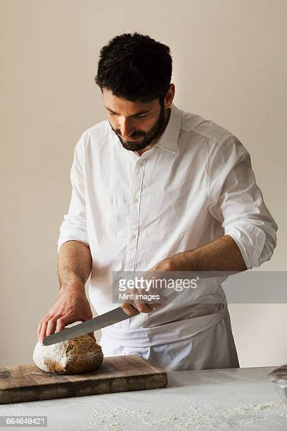 Baker slicing a freshly baked loaf of bread with a bread knife.