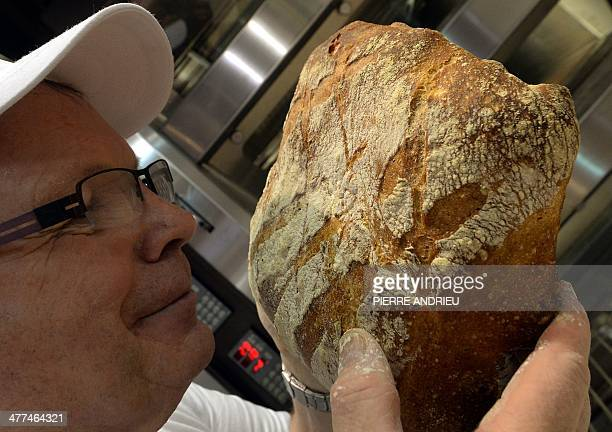 A baker smells a loaf of bread during Europain 2014 a World Bakery Patisserie and Catering exhibition held in Villepinte north of Paris on March 9...