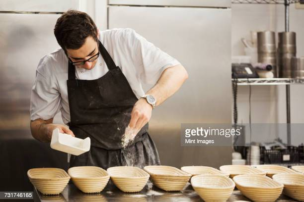Baker sprinkling flower into proving baskets in the kitchen