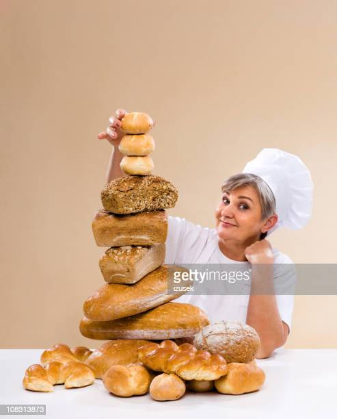 baker stacking up fresh bread - izusek stock pictures, royalty-free photos & images