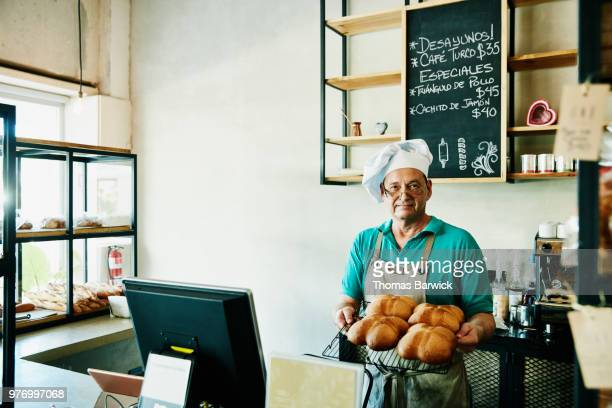 Baker standing behind counter in shop holding tray of freshly baked bread