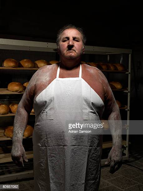 Baker standing in front of rack of fresh bread