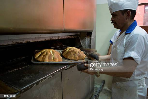 A baker takes a tray of pan de muerto out of an oven at La Ideal bakery in Mexico City Mexico on Thursday Oct 24 2013 The pan de muerto or bread of...