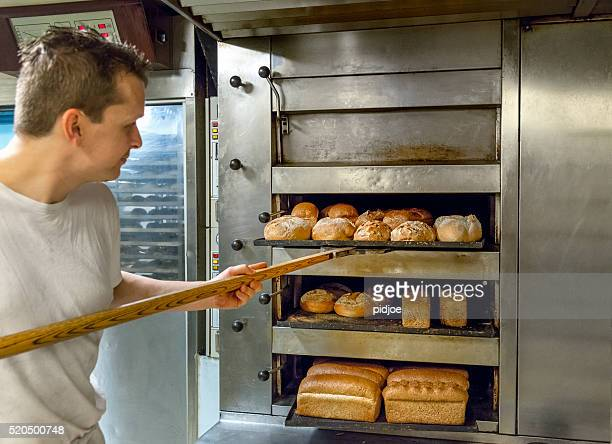Baker taking bread out of oven