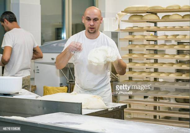Baker throwing leavened dough on working table