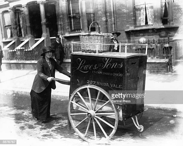 A baker wheeling her bread barrow through a London street