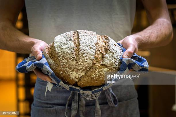 baker with fresh, warm bread. - loaf of bread stock pictures, royalty-free photos & images