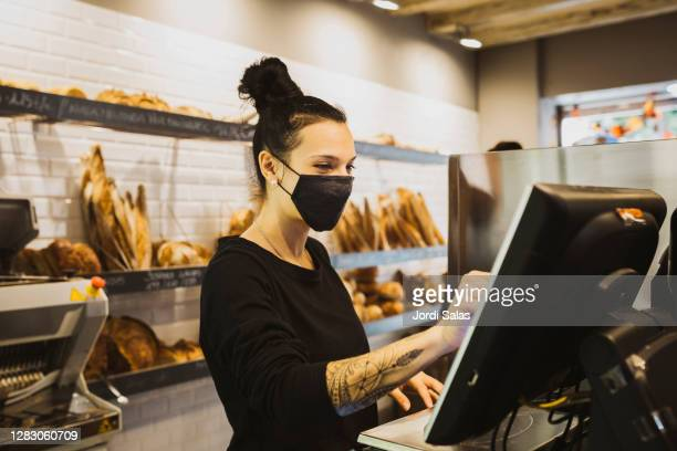 baker woman typing the cash register machine in a bakery - weibliche angestellte stock-fotos und bilder
