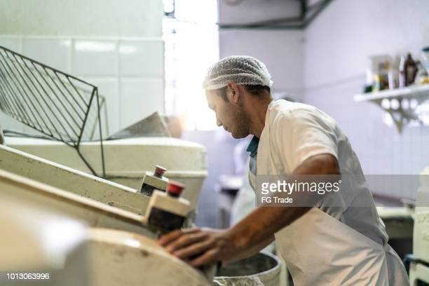 Baker working making a bread in the professional kitchen at Bakery