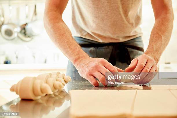 A baker working on a floured surface, rolling up dough squares into croissant shapes before baking.