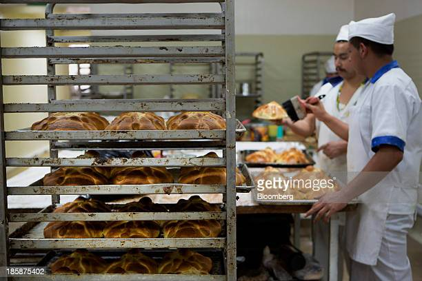 Bakers add syrup to loaves of pan de muerto at La Ideal bakery in Mexico City Mexico on Thursday Oct 24 2013 The pan de muerto or bread of the dead...