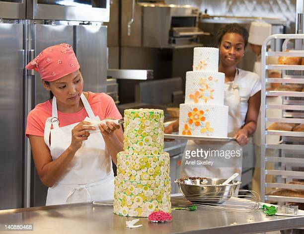 Bakers decorating elaborate cakes in bakery