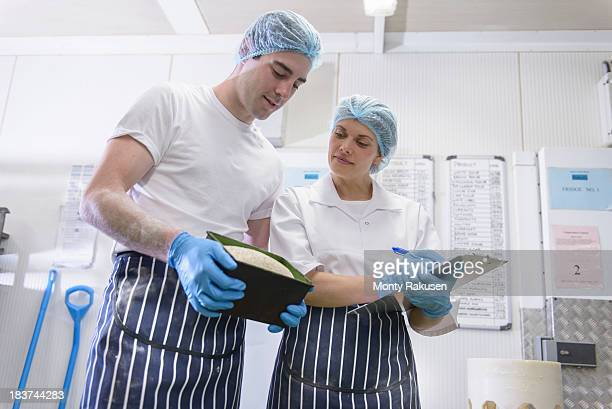 Bakers inspecting freshly baked bread in tin
