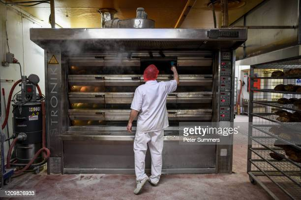 A bakers is seen checking on bread in an oven at The Bread Factory on April 14 2020 in London England During the COVID19 outbreak and lockdown the...