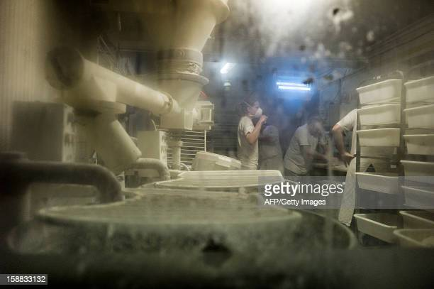 Bakers mold bread paste before baking it on December 27 2012 in a bakery of Ecole en Bauges French Alps AFP PHOTO / JEFF PACHOUD