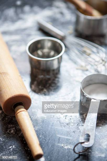Baker's Table with Rolling Pin Measuring Cup Whisk and Cookie Cutter Selective Focus