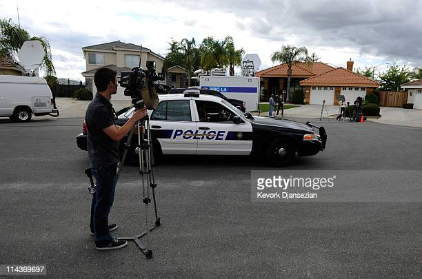 Bakersfiled Police cruiser drives by news media trucks parked on a residential street outside the home of Mildred Patricia Baena former household...