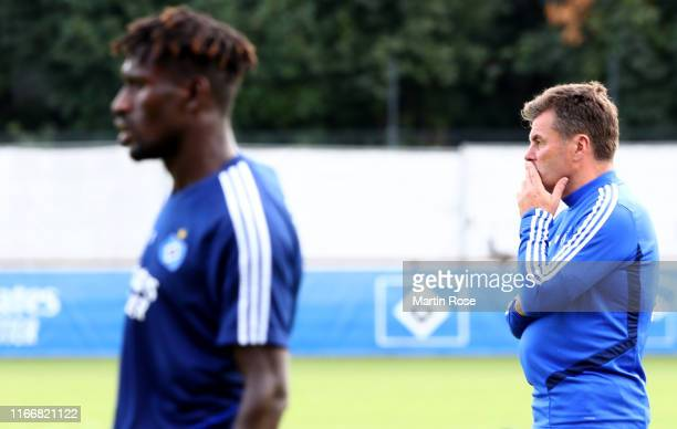 Bakery Jatta of Hamburger SV is seen during a training session whilst head coach of Hamburger SV Dieter Hecking looks on at Volksparkstadion on...