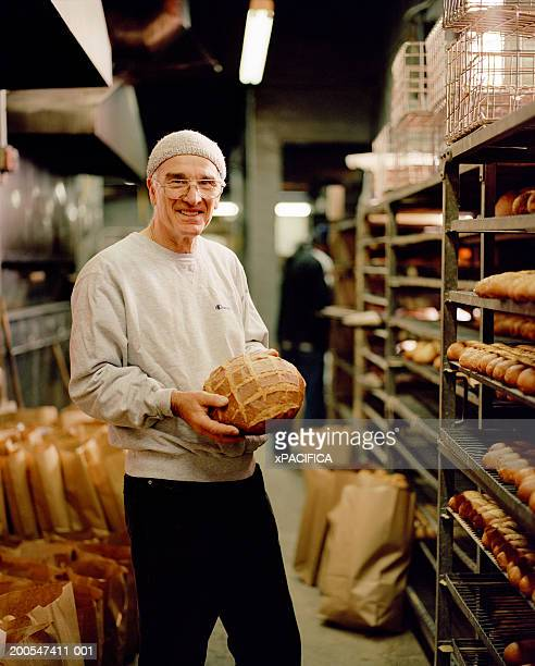 Bakery owner holding bread in storage room, portrait