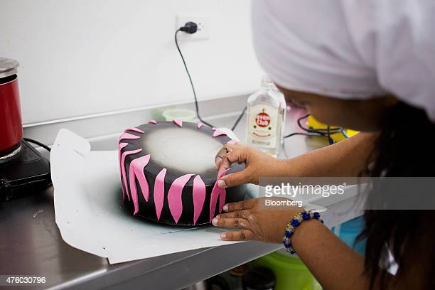 Bakery owner Kirenia Mulen Faez works on a cake for a quinceanera celebration in Havana Cuba on Saturday May 9 2015 Faez's small business making...