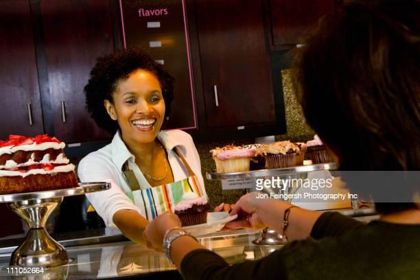Bakery owner serving customer cupcake