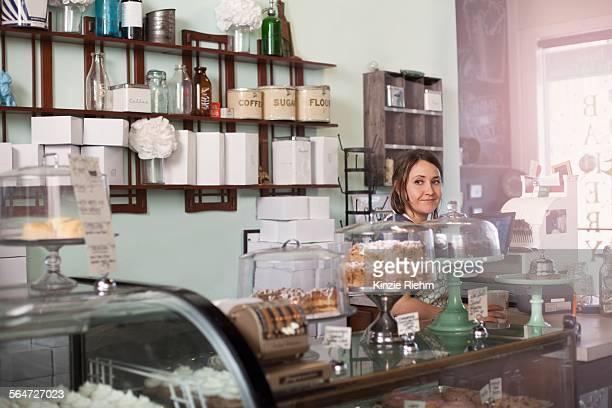 bakery owner standing behind counter of vegan, allergy-friendly bakery - キャニスター ストックフォトと画像