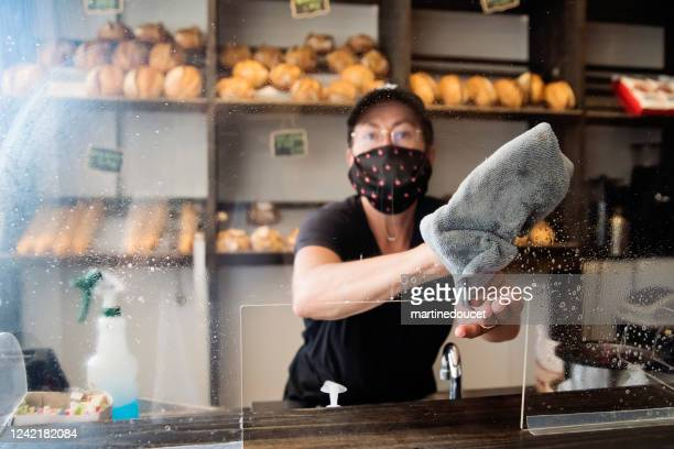 """bakery owner wiping down surfaces wearing mask. - """"martine doucet"""" or martinedoucet stock pictures, royalty-free photos & images"""