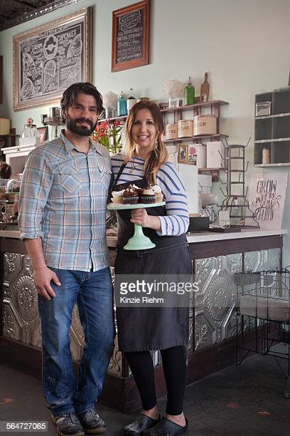 Bakery owners carrying tray of allergy-friendly cupcakes