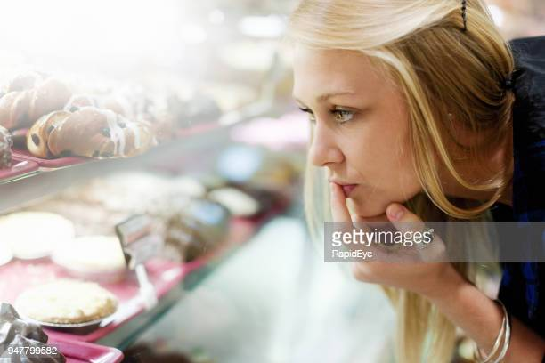 bakery shelves tempt young woman in a supermarket - temptation stock pictures, royalty-free photos & images