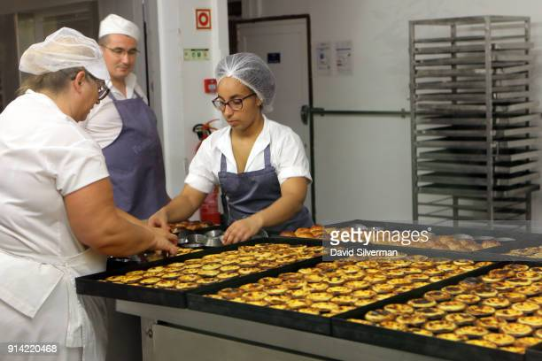 Bakery staff prepare Pastel de nata a traditional Portuguese sweet egg pastry at the famous Pastéis de Belém bakery and cafe on October 1 2016 in the...