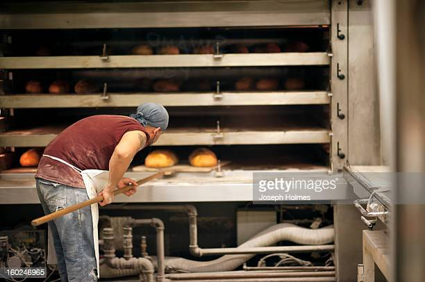 CONTENT] A bakery worker checks the bread in an oven at Amy's Bread a commercial bakery in New York City's Chelsea Market
