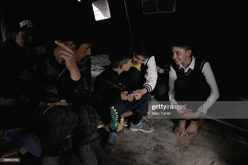 Bakht, Wali, Yasseen and Habib Khan from Laghdar and Jalalabad in Afghanistan, play on their mobile phones to help pass the long afternoons in the camp known as 'The Jungle' where they are living, on May 10, 2016 in Calais, France. The boys spend much of the night time trying to gain access to vehicles heading from France to the UK where they hope to claim asylum. The British government is currently considering a move to take in up to 3000 children from refugee camps around the world and around 100 from Calais after coming under pressure to rethink their stance on not taking in vulnerable and unaccompanied child refugees.