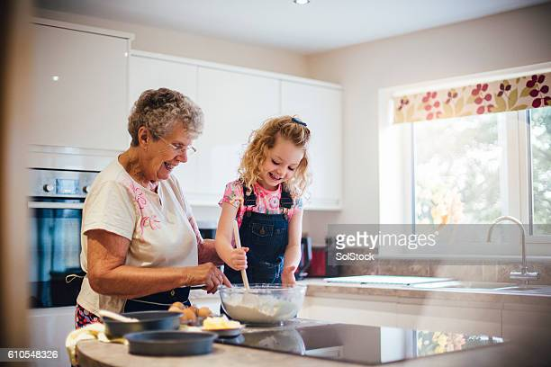 baking a cake with grandma - granddaughter stock pictures, royalty-free photos & images