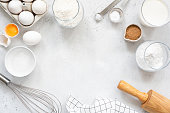 Baking and cooking ingredients on bright grey background