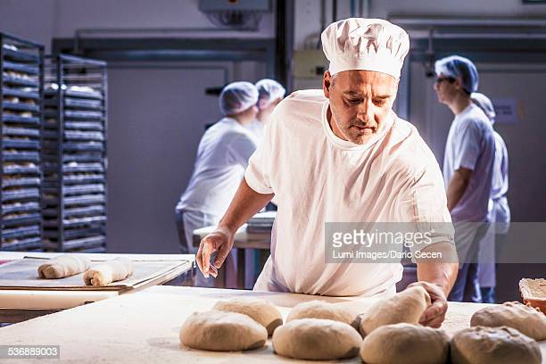 Baking bread, chef controlling dough