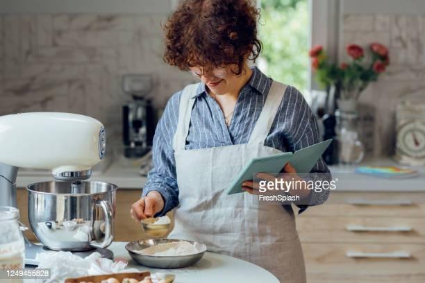 baking cookies: een lachende vrouw na een live cooking video sessie online tijdens het maken van cookies thuis - volgen activiteit stockfoto's en -beelden