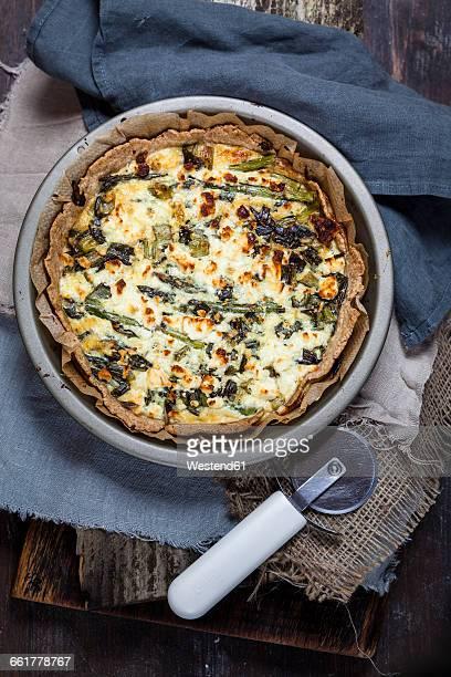 Baking dish of green asparagus tart with feta cheese