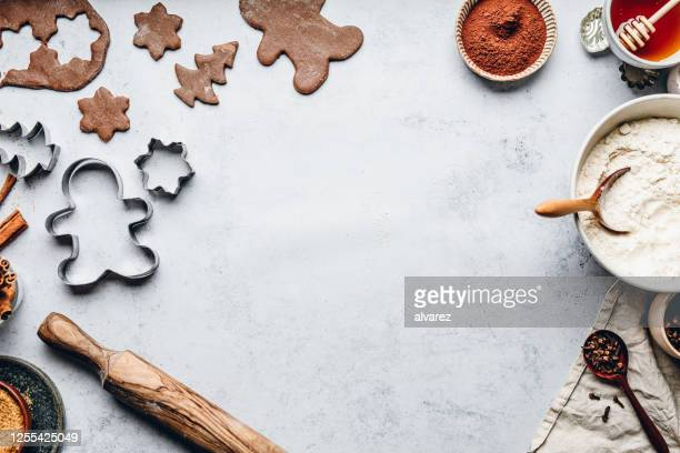 baking gingerbread man christmas cookies in kitchen - gingerbread men stock pictures, royalty-free photos & images